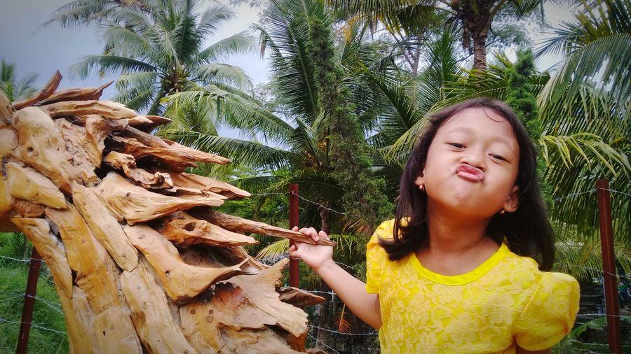 Portrait of girl holding plant against trees