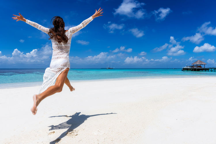 Happy woman in white dress enjoys a tropical beach in the Maldives Sea Sky Water Land Beach Horizon Over Water Horizon Leisure Activity One Person Beauty In Nature Sunlight Human Arm Nature Real People Scenics - Nature Holiday Arms Raised Hairstyle Limb Arms Outstretched Outdoors Freedom Maldives Caribbean Jumping Dress White Woman Travel Tropical Climate Tropics Happy Happiness Enjoying Life Fun