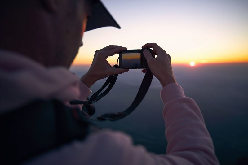 Man using mobile phone for photographing sunset point against sky