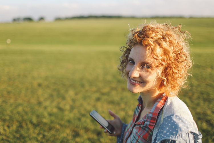 Beauty In Nature Blonde Casual Clothing Curly Hair Field Focus On Foreground Girl Grassy Green Color Leisure Activity Lifestyles Nature Non-urban Scene Person Plantation Rural Scene Scenics Sunset Tranquility