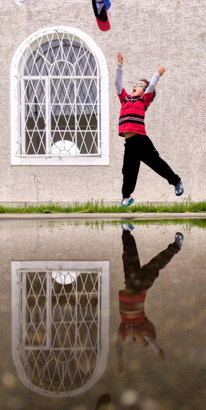 Reflection Of Boy In Pond Throwing Cap While Jumping On Field Against Building