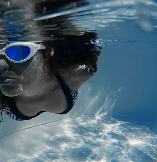 Close-up of woman with goggles swimming in pool