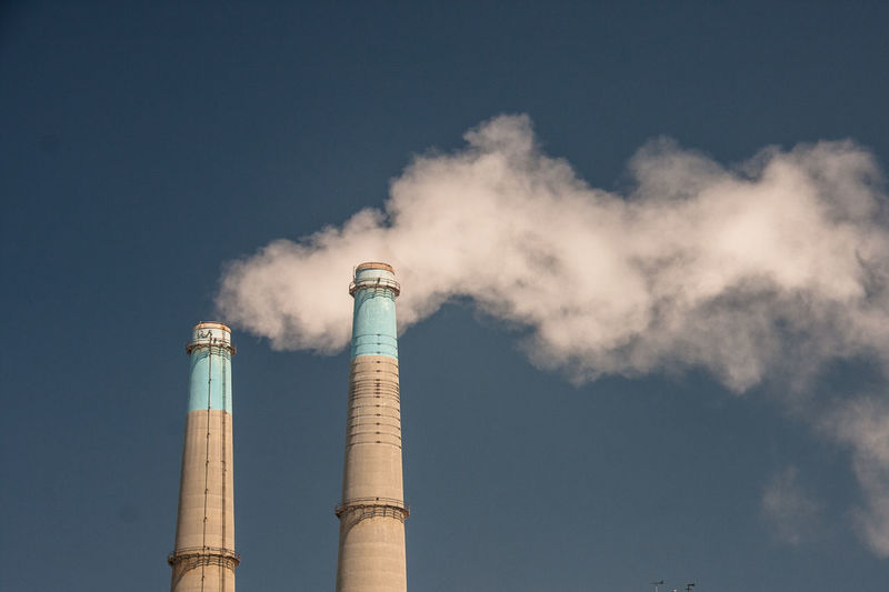 Low angle view of smoke stacks against clear sky
