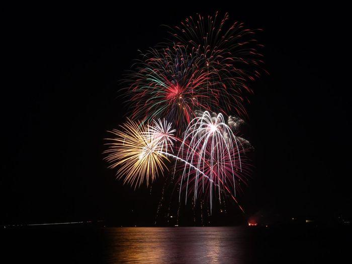 Illuminated fireworks over lake against sky at night