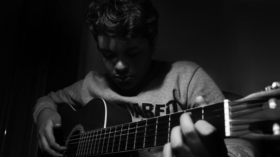 Young man playing guitar while sitting in darkroom