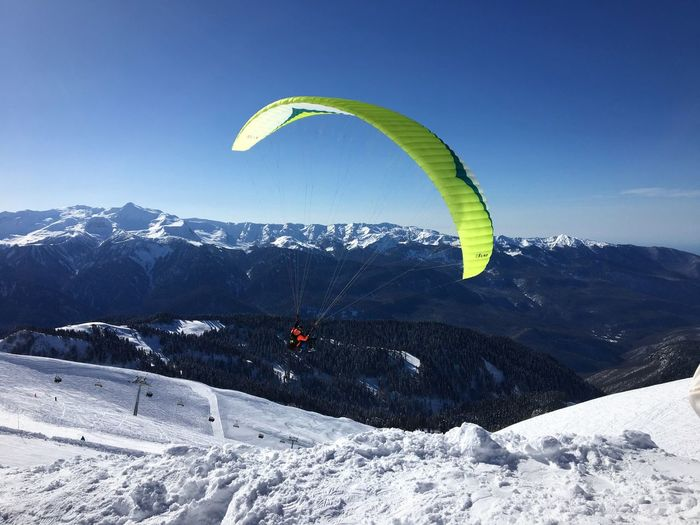 Person Paragliding Over Snowy Field Against Sky