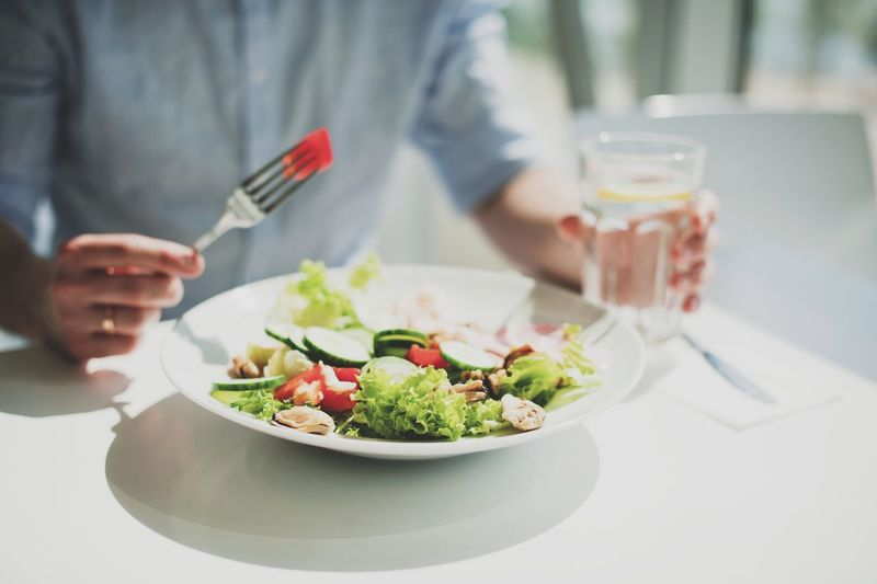 a young man eats a salad in a light restaurant Food And Drink Food Freshness Table Midsection Vegetable Healthy Eating Ready-to-eat Lifestyles Focus On Foreground Human Hand Meal Indoors  Hand Real People Holding Plate Salad One Person Wellbeing