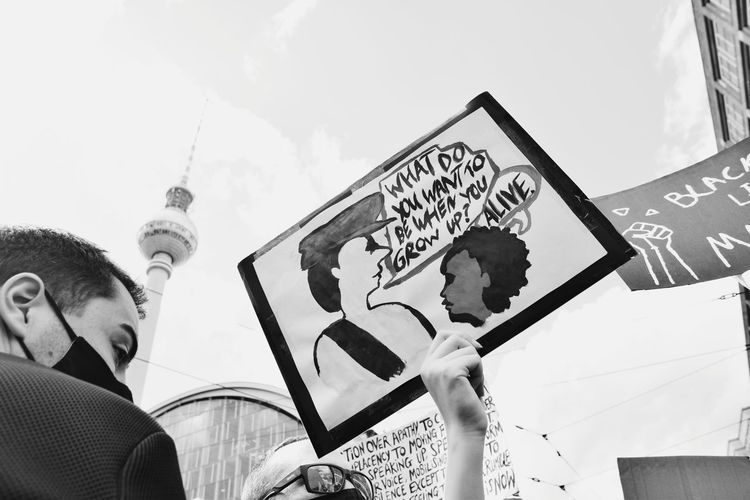Low angle view of man holding text against sky