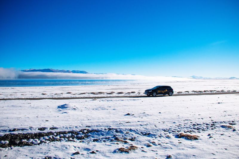 Cars on snow covered land against clear blue sky