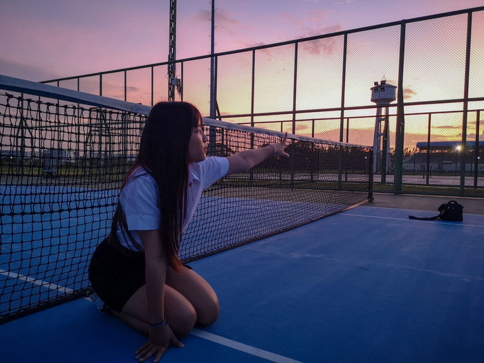 Woman sitting on court against sky during sunset
