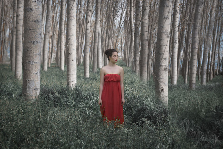 Young woman standing at forest