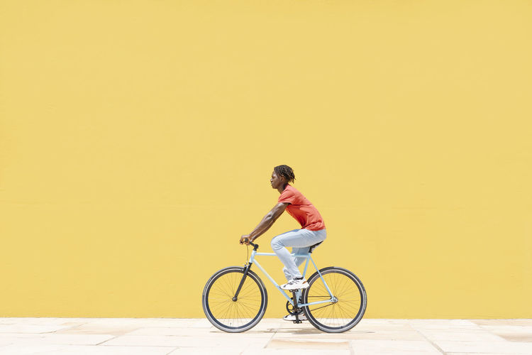 Man riding bicycle on yellow wall