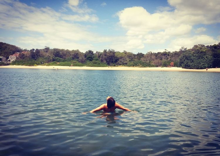 Rear view of woman relaxing in lake against sky