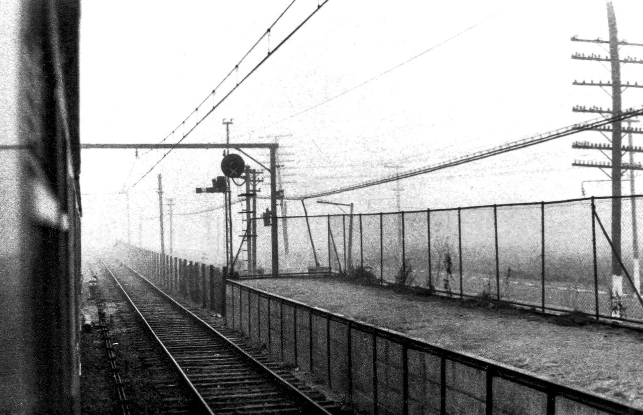 cable, railroad track, transportation, power line, railing, connection, real people, one person, bridge - man made structure, rail transportation, day, outdoors, electricity, full length, electricity pylon, technology, nature, sky, people