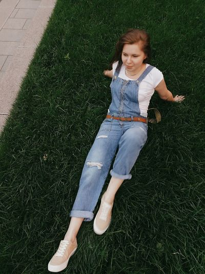 High angle view of young woman looking away while lying on grassy field