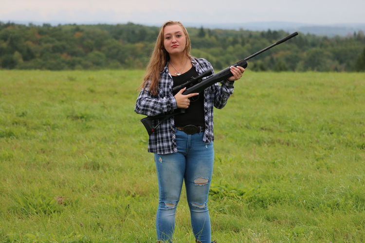 Senior photo shoot Adult Beautiful Woman Casual Clothing Day Field Front View Grass Gun Hairstyle Holding Land Leisure Activity Looking At Camera Nature One Person Plant Portrait Real People Standing Weapon Young Adult