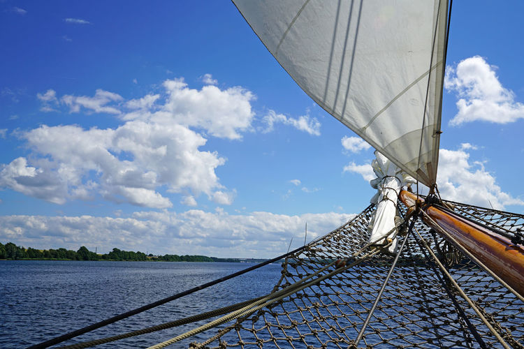 Cropped Boat Sailing On River Against Blue Sky
