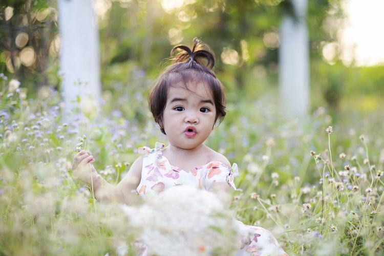 Portrait of cute girl standing on field