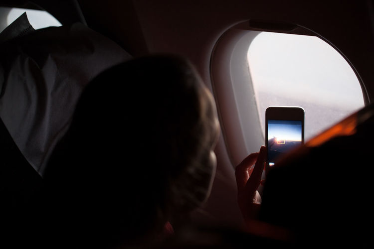 Close-Up Of Woman Photographing Through Airplane Window