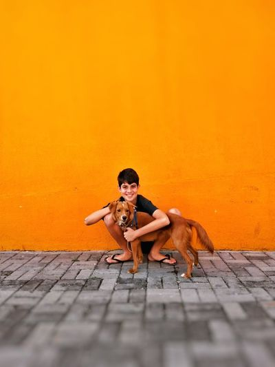 Portrait of smiling boy embracing dog while crouching on street