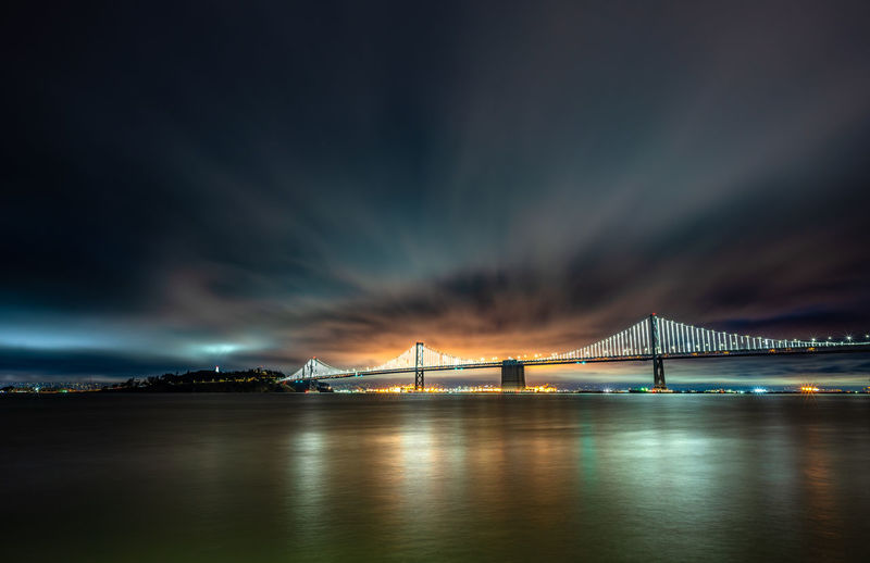 Illuminated bridge over river against cloudy sky