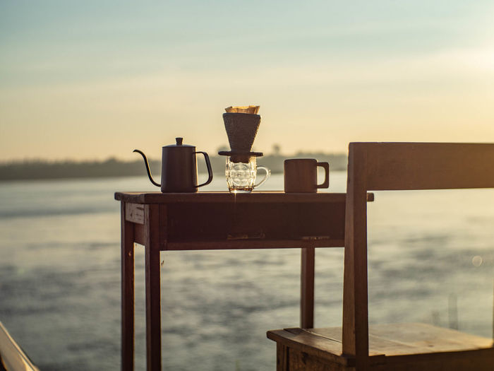 Close-up of drink on table by sea against sky