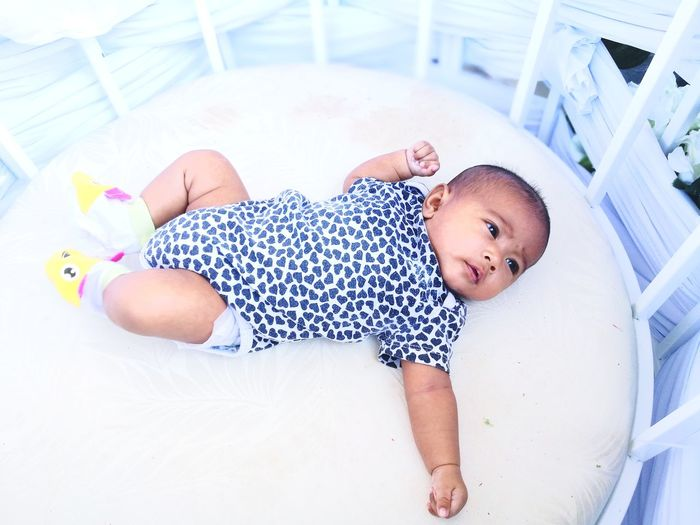 Cute baby girl lying in crib
