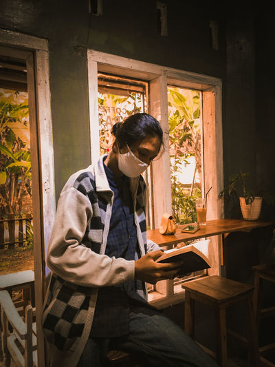 Woman wearing mask reading book while sitting at cafe