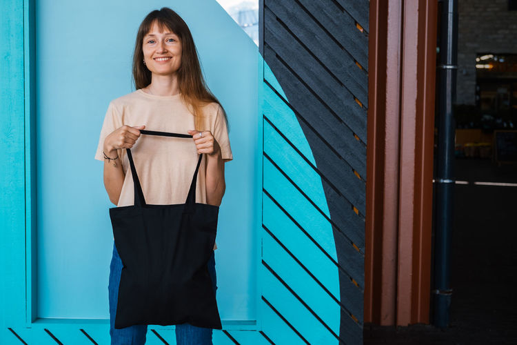 Woman holding black canvas tote bag. bag mockup for design.