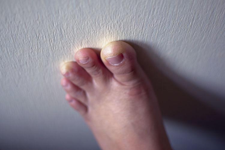Close-up of human foot touching wall