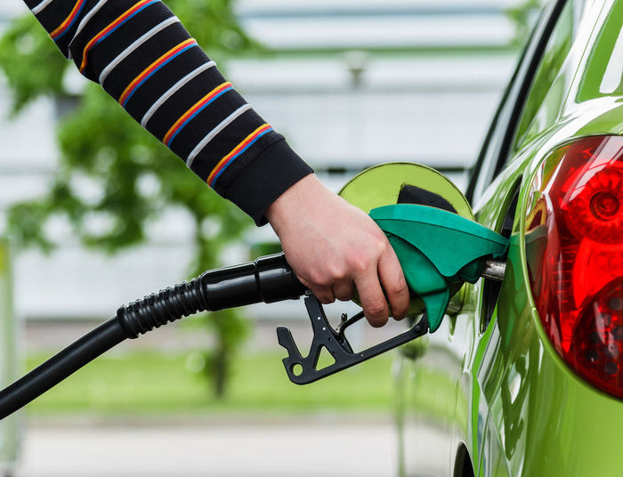 Cropped hand of person refueling car