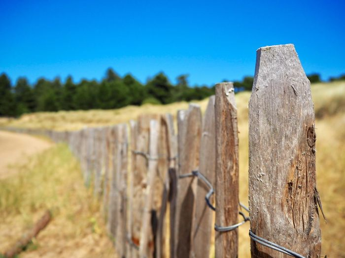 Close-Up Of Wooden Fence On Field Against Clear Sky