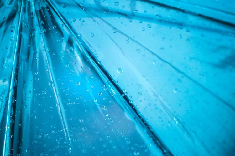 Full frame shot of raindrops on blue water