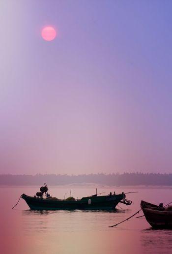 Fishing boat moored on lake against sky