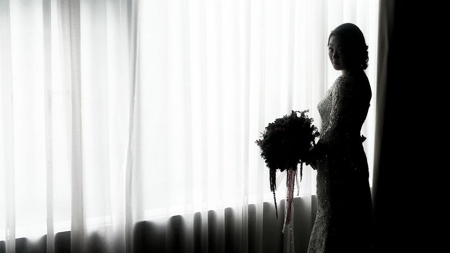 Portrait Of Bride Standing In Dark Room