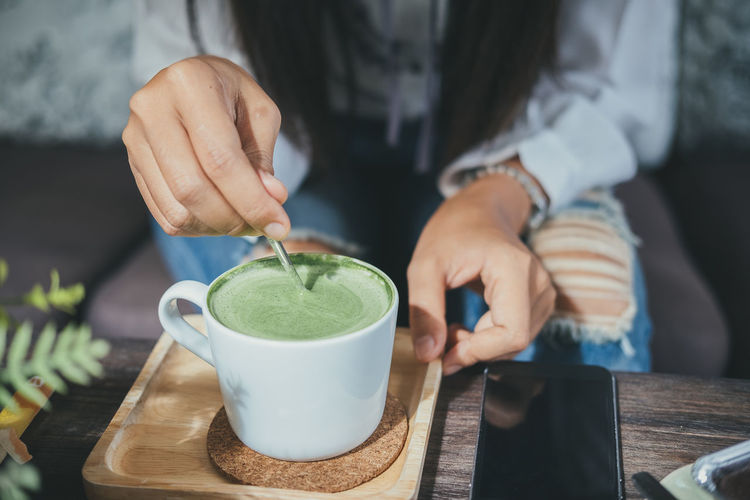 Woman holding spoon and stirring hot green tea matcha latte at cafe. Adult Cup Drink Food Food And Drink Freshness Front View Glass Hand Holding Human Body Part Human Hand Indoors  Midsection Mug One Person Preparation  Real People Refreshment Table Tea Cup