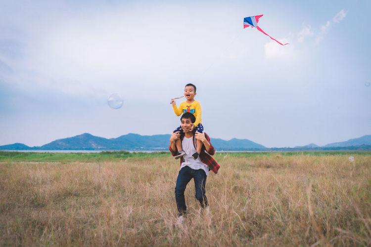 Full length of man flying kite on field against sky