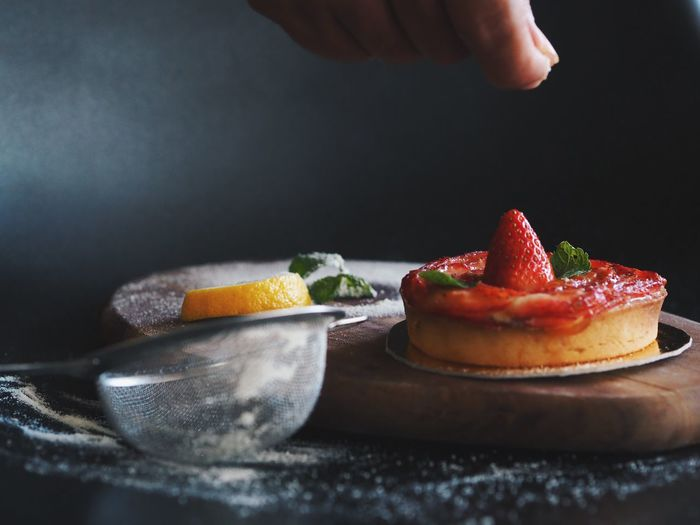Master chef master delicious strawberry tart over dark background. Strawberry Tart Berry Fruit Finger Food Food And Drink Freshness Fruit Hand Healthy Eating Holding Human Body Part Human Hand Indoors  One Person Plate Preparation  Real People Selective Focus Strawberry Table Table Knife Unrecognizable Person Wellbeing
