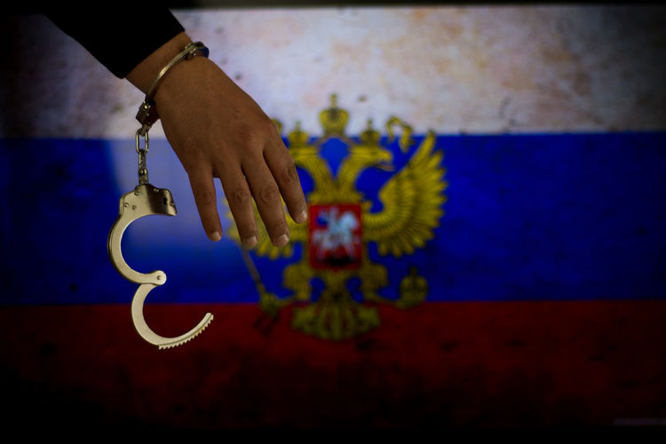 Cropped hand of male criminal with handcuffs against russian flag