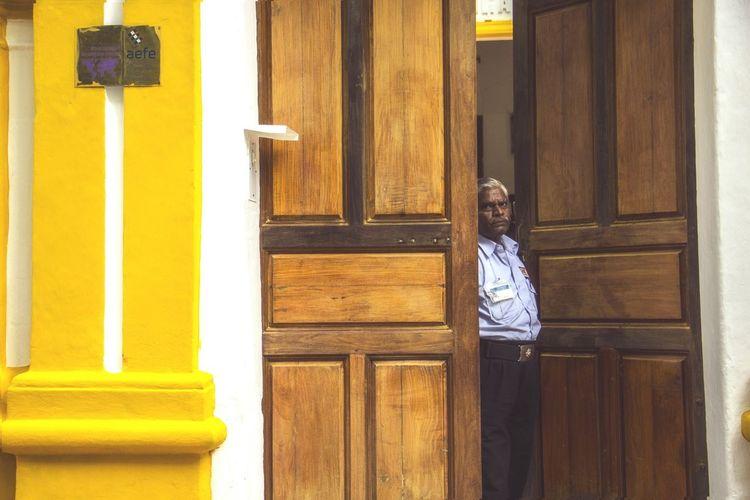 Portrait Of Security Guard Standing Amidst Door