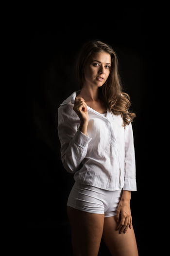 Black Background Three Quarter Length Beauty One Person Beautiful Woman Young Adult Studio Shot Portrait Women Young Women Standing Front View Looking At Camera Adult Long Hair Hairstyle Indoors  Fashion Hair Contemplation Temptation Dark