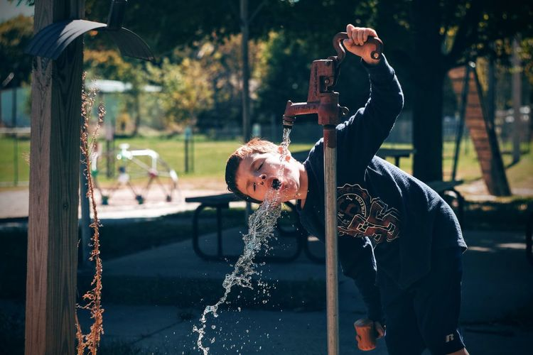 Boy drinking from water pump in park