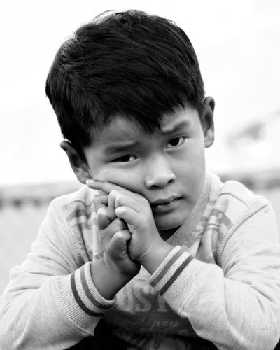 Close-Up Portrait Of Boy With Hands Clasped Sitting Outdoors