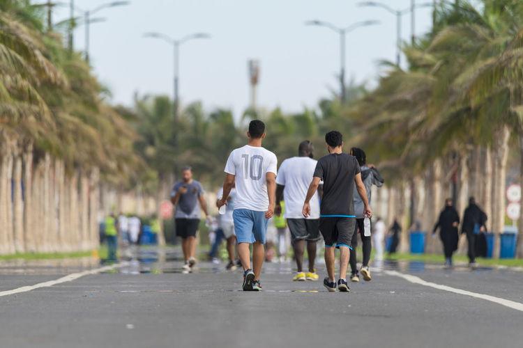 Rear view of men walking on road in city