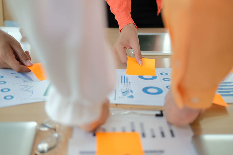 Cropped image of business person holding adhesive notes on table at office