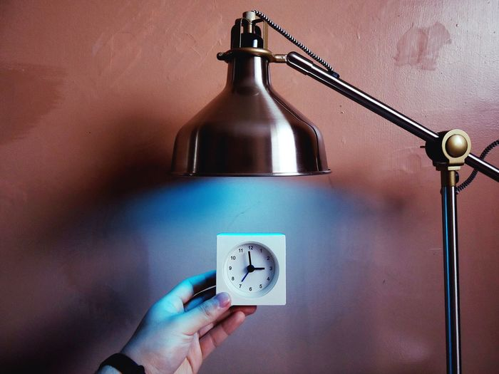 Cropped Hand Holding Small Clock Under Electric Lamp