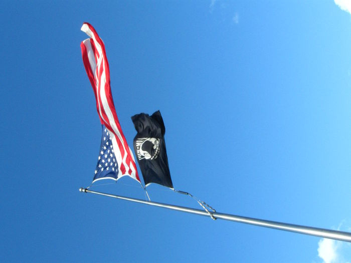 Low Angle View Of American And Pow-Mia Flag Against Blue Sky On Sunny Day