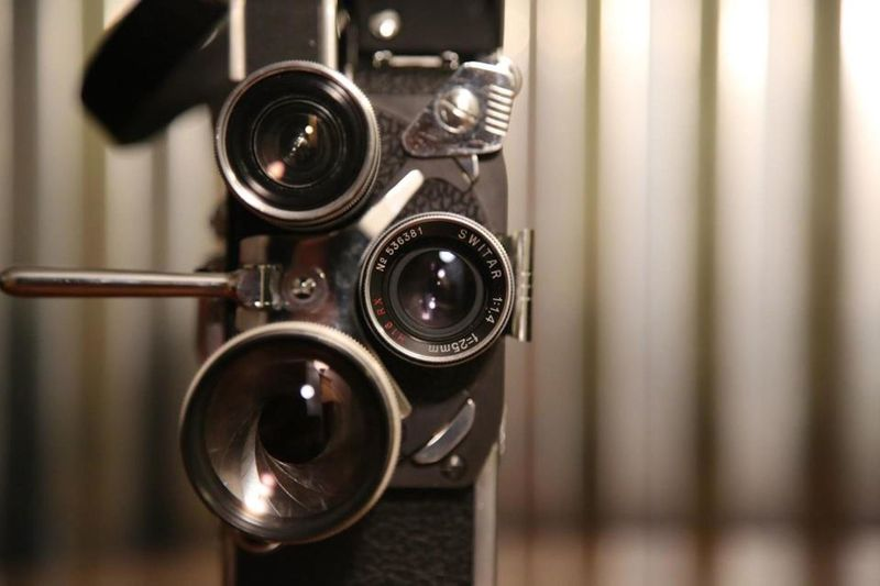 8mm Handheld Motion Picture Camera. A vintage 8mm film camera still life.. Close-up No People Technology Selective Focus Movie Camera Antique Lens - Optical Instrument Studio Shot Focus On Foreground Single Object Lens - Eye Still Life Camera Film 8mm Arts Culture And Entertainment Spool Film Industry Photography Themes In A Row Industry Business MOVIE Retro Styled Copy Space Cut Out