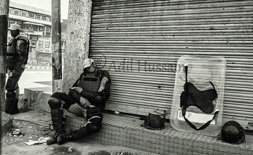 """Indian paramilitary cop taking nap during a curfew in Old Srinagar, the summer capital of Indian-administered Kashmir. Authorities on Saturday clamped curfew like restrictions in parts of Old Srinagar to foil proposed rally of pro-freedom groups towards Martyrs Graveyard """"Eid-Gah"""" on the martyrdom anniversary of two prominent pro-freedom figures Mirwaiz Molvi Farooq and Ab. Gani Lone on May 21, 2016. While as a complete shutdown was observed across Kashmir valley on the martyrdom anniversary of slain leaders. Taking Photos Documentary The Photojournalist - 2016 EyeEm Awards Curfew Sleepingonstreet Sleepingonthejob Downtown Storyteller Popular Photooftheday Photojournalism Srinagar  Streetphoto EyeEm Best Shots - The Streets EyeEm Masterclass ASIA Check This Out News Press Photography"""
