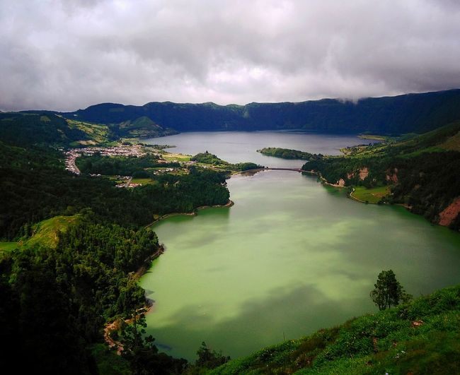 High angle view of lake against mountains and cloudy sky